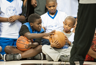 Students examine a vintage laced basketball at a Black Fives Foundation event at the Barclays Center in collaboration with the Brooklyn Nets. (Photo: Nancy Borowick)