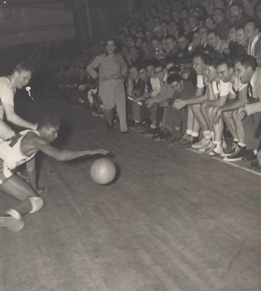 Harlem Globetrotters guard Marques Haynes dribbles to elude a defender as spectators laugh, 1949.