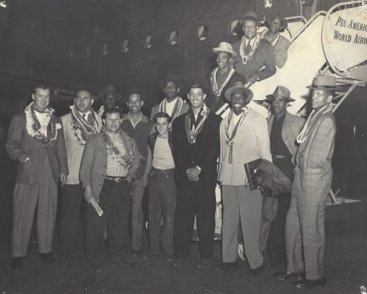 "The Harlem Globetrotters are welcomed upon arrival in Hawaii, circa 1952. Front row, left to right: Abe Saperstein, unk., unk., unk., ""Babe"" Pressley, Buiey. Back row (left to right): Unknown, unknown, unknown, unknown, Marques Haynes, unknown, unknown,unknown."